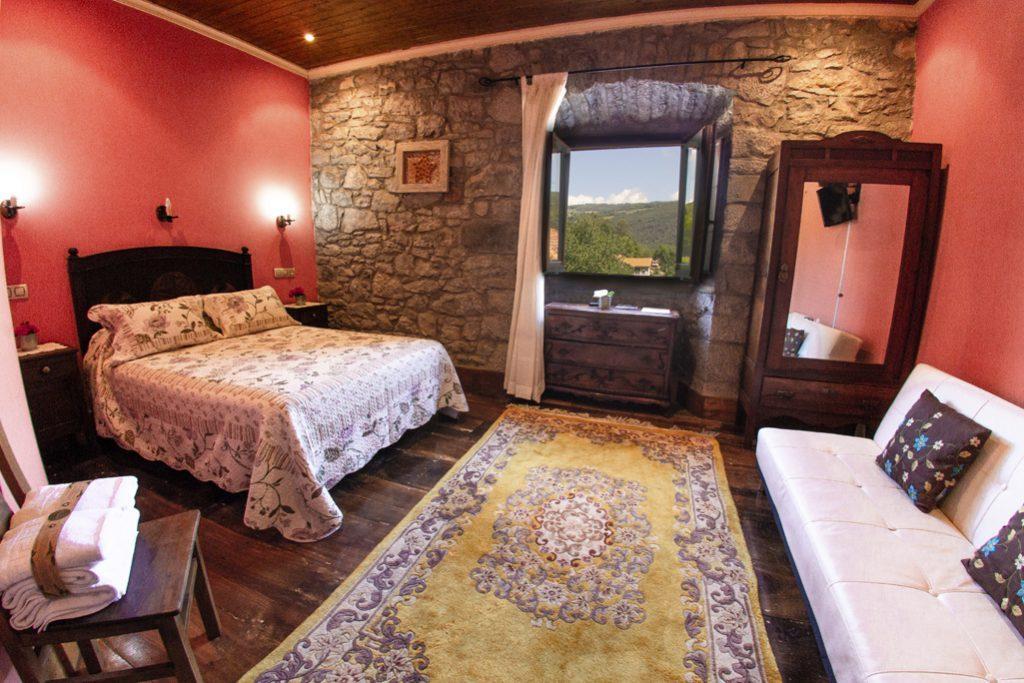 Habitación roja con pared de piedra y vistas exteriores