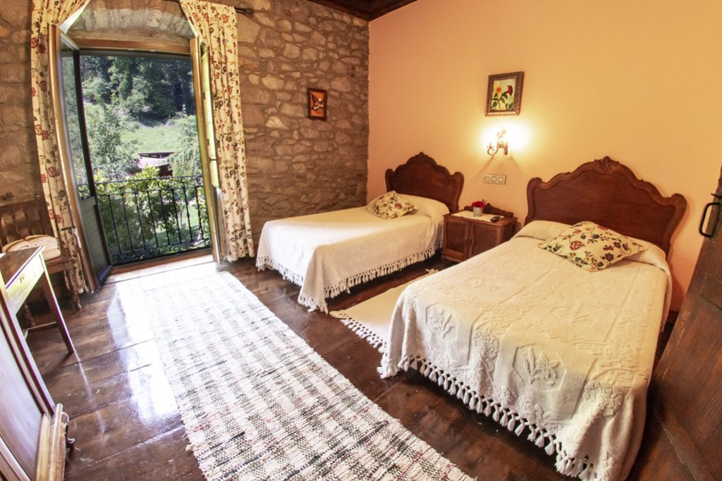 Habitación crema con dos camas individuales y balcón